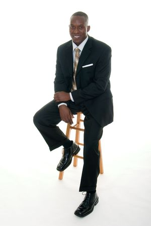 casually: Handsome African American man in a black business suit casually sitting on a stool.