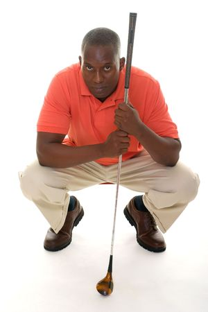 lining up: Casual young African American man in a bright orange golf shirt with a golf club lining up a putt.