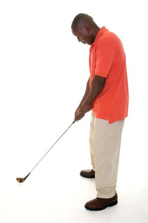 lining up: Casual young African American man in a bright orange golf shirt holding a golf club to lining up a drive and preparing to swing. Stock Photo