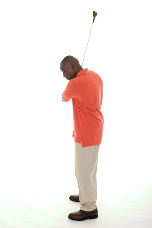 Casual young African American man in a bright orange golf shirt swinging a golf club. photo