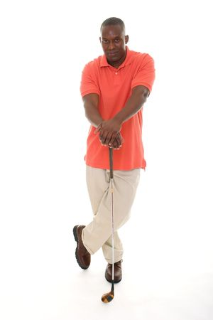 Casual young African American man in a bright orange golf shirt holding a golf club.
