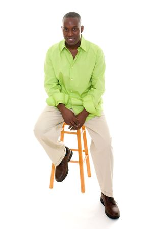 Casual young African American man standing in a bright green shirt sitting comfortably on a stool. Stock Photo