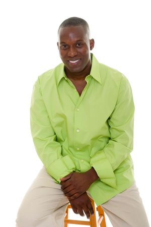 Casual young African American man standing in a bright green shirt sitting comfortably on a stool. photo