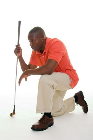 Casual young African American man in a bright orange golf shirt with a golf club lining up a putt. photo