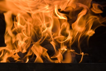 Hot flames from a burning charcoal fire.