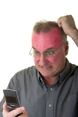 Very angry man with a exaggerated facial expression looking at a cellphone and turning red in the face. photo