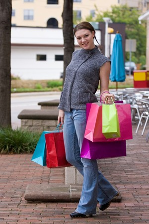 Attractive young happy woman with colorful shopping bags walking in an urban city environment. photo