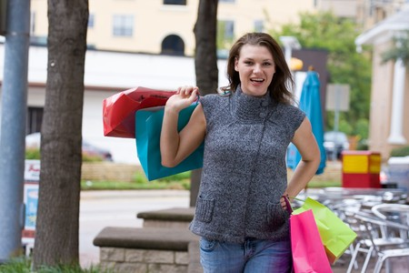 Attractive young happy woman with colorful shopping bags walking in an urban city environment. Stock Photo - 4504455