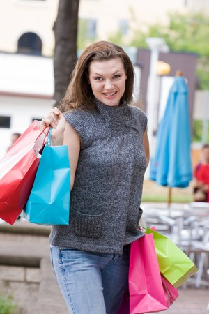 Attractive young happy woman with colorful shopping bags walking in an urban city environment. Banco de Imagens