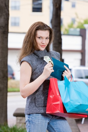 else: Young woman on a shopping trip holding colorful shopping bags, counting her money, thinking about what else she can buy.