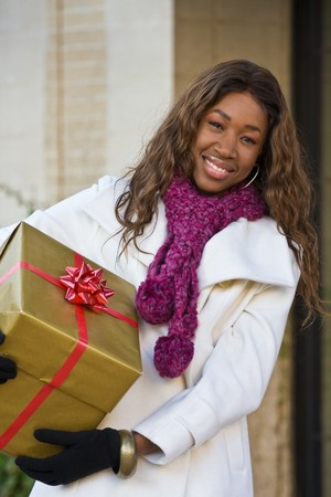 Attractive young happy woman walking in an urban city environment and holding a Christmas gift wrapped in gold paper. photo