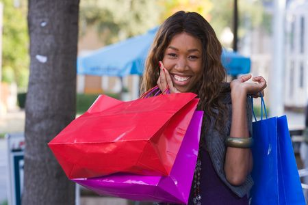 Attractive young happy African American woman walking in an urban city environment and carrying shopping bags. Stock Photo - 5841334