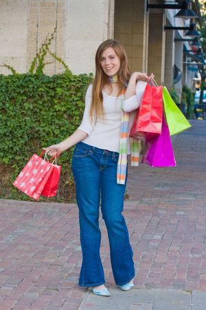 Attractive young happy woman with red hair walking in an urban city environment and carrying shopping bags. Stock Photo - 5841342