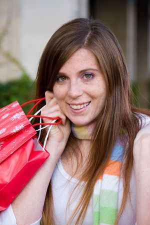 Attractive young happy woman with red hair walking in an urban city environment and carrying shopping bags. Stock Photo - 5841338