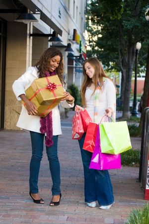 Two attractive young happy women walking in an urban city environment and carrying Christmas gifts. photo