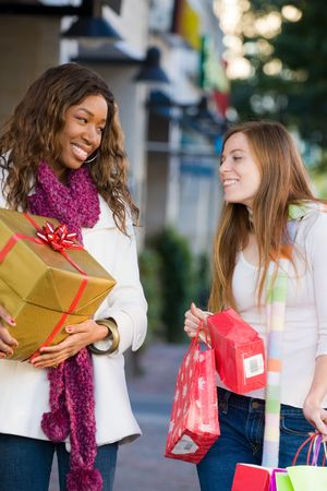 Two attractive young happy women walking in an urban city environment and carrying Christmas gifts. Stock Photo - 5841350