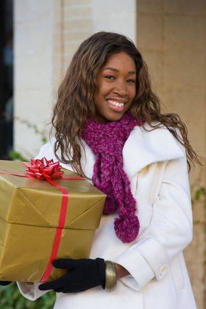 Attractive young happy African American woman walking in an urban city environment and holding a Christmas gift wrapped in gold paper.