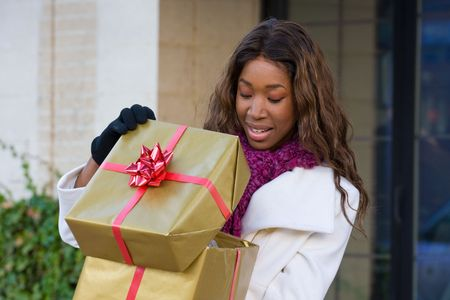 Attractive young happy African American woman walking in an urban city environment and holding a Christmas gift wrapped in gold paper. photo