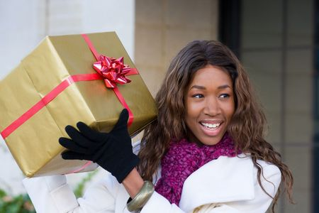 Attractive young happy African American woman walking in an urban city environment and holding a Christmas gift wrapped in gold paper. Stock Photo - 5841345
