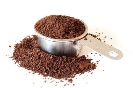 Ground coffee spilling out of a full coffee measure. Shot on white background. Focus is on the edge of the cup. Coffee in the foreground is out of focus. Stock Photo
