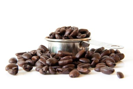 Whole coffee beans spilling out of a full coffee measure. Shot on white background. Focus is on the edge of the cup. Beans in the foreground are out of focus.