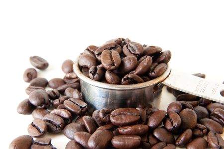 Whole coffee beans spilling out of a full coffee measure. Shot on white background. Focus is on the edge of the cup. Beans in the foreground are out of focus. Stock Photo - 6252328