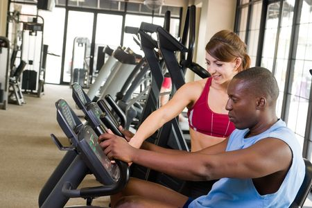 Man and woman exercising together at a fitness center on a stationary bicycle exercise machine.  Woman could be a personal fitness trainer. Focus is on the man in the foreground. Stock Photo - 6321017