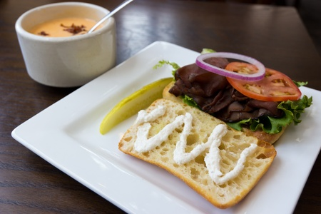 pleasing: Pleasing presentation of a roast beef sandwich and a cup of cheese soup for lunch at a restaurant.