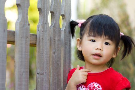 울타리 옆에 아시아 중국 어린이 스탠드의 가까이 스톡 콘텐츠