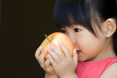 Little child hold a red apple close to her face