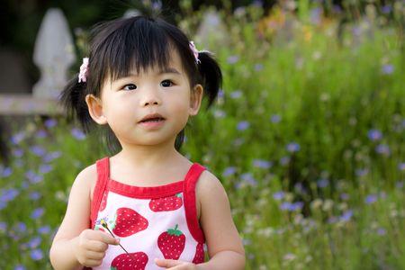작은 아시아 아이 그녀의 손에 꽃을 잡아