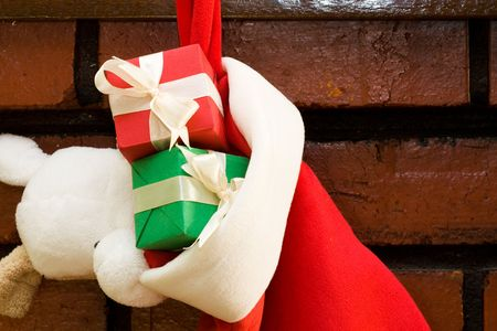 mantel: Gift boxes with ribbon in a Christmas sock hanging on fireplace mantel