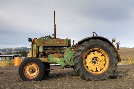 Rusty old tractor sits alone in the field on a farm photo