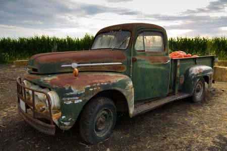 Rusty old truck fit with pumpkin sits alone in the field on a farm