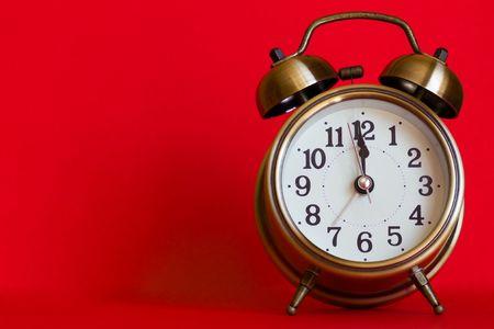 Stylish classic alarm clock on red background Stock Photo