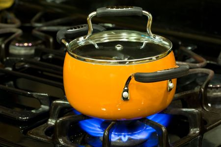 Covered non stick sauce pan on a stove top with fire is turned on Imagens