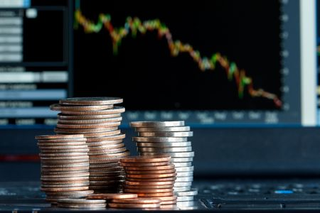 Stacks of coins  and a down trend chart as the background photo