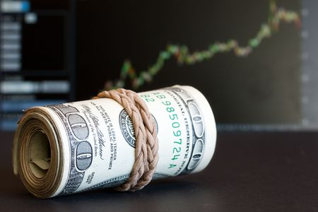 100 dollar notes with graph as the background photo