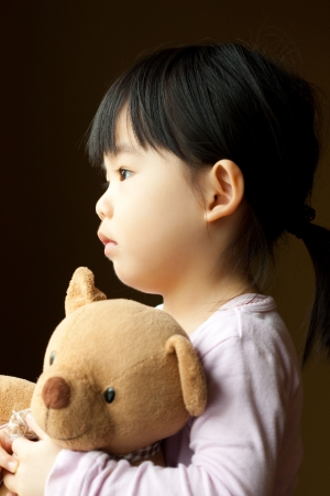Sad little girl holds a teddy bear looks into the window. Resentment and expectation