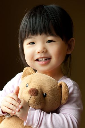 Smiling little child holding a teddy bear in her hand photo