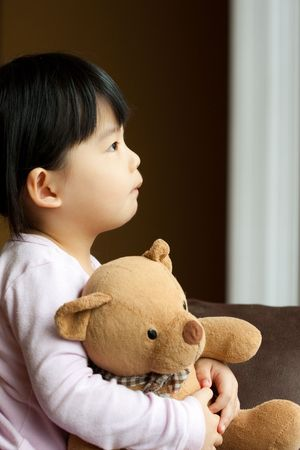 Sad little girl holds a teddy bear looks into the window. Resentment and expectation photo