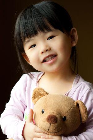 pijama: Sonriente a ni�o peque�o con un oso de peluche en su mano