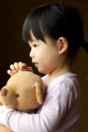 pijama: Ni�a con un oso de peluche en su mano
