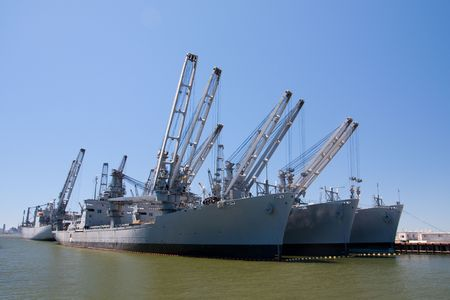 Cargo ships with cranes park at a harbor photo