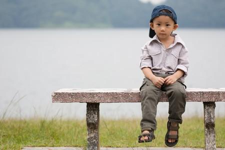 아시아 어린 소년 공원에서 벤치에 앉아