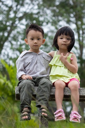 infants: Two little kids dating with hand lifts onto shoulder in a park Stock Photo