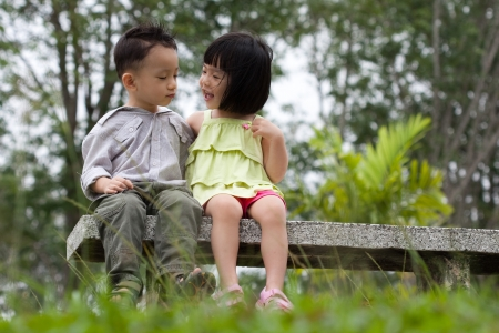 Two little kids dating with hand lifts onto shoulder in a park Stock Photo