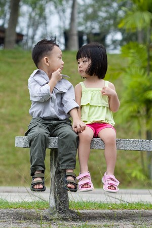 shy woman: Two little kids having a date in park Stock Photo