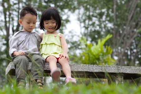 loving hands: Two little kids dating with hand lifts onto shoulder in a park Stock Photo