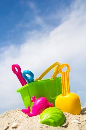 juguetes: Cubo de ni�o, spade y otros juguetes en una playa tropical contra el cielo azul Foto de archivo